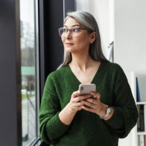 Photo of gray-haired serious businesswoman using cellphone